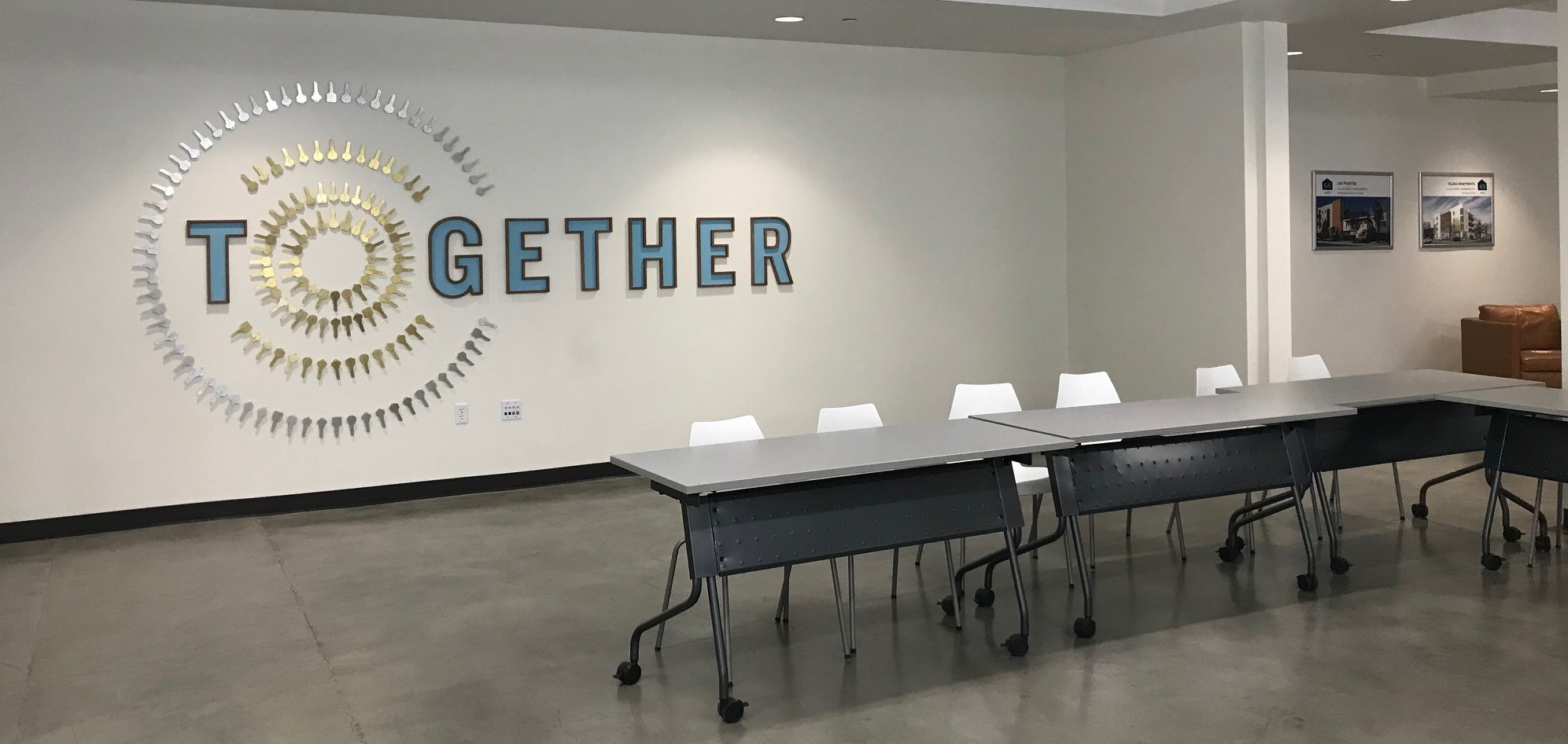 A room with the word together spelled on the wall in large lettering, with keys forming the letter o. There is also a table and chairs set up in the room for gatherings.