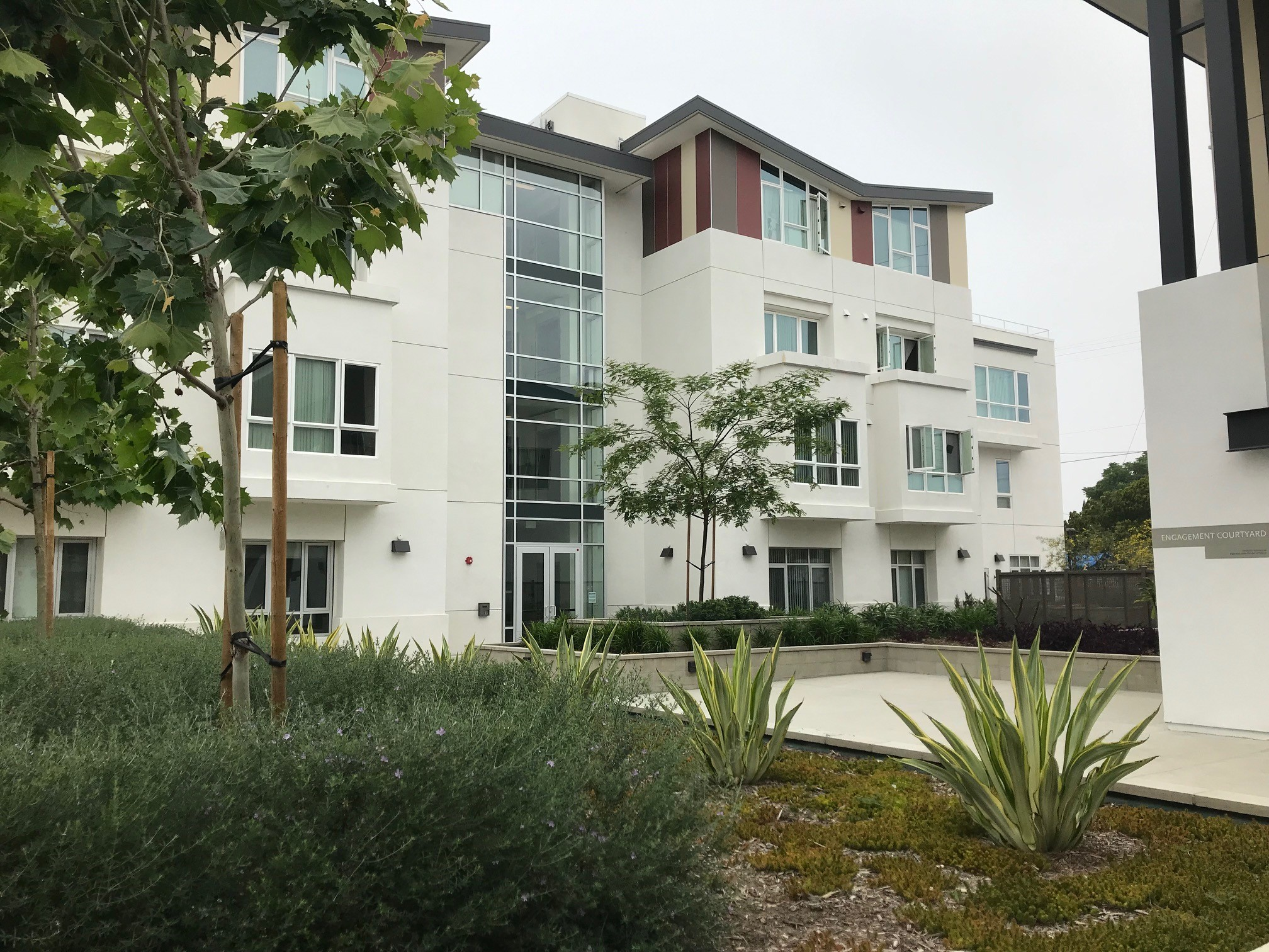Image of large building with lots of glass windows and a slanted roof-line with alternating earth-toned colors. The ground is landscaped with trees and plants.