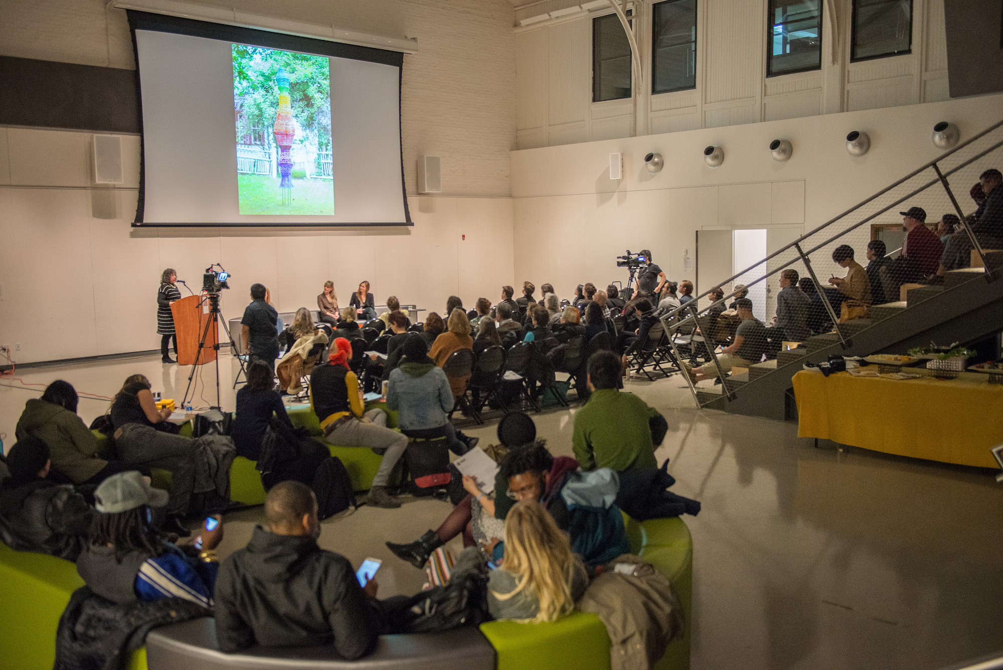 "A photograph of a large crowd of people listening to artist Antonia Perez as she speaks about her artwork. Antonia stands to the far left at a podium in a large amphitheater with white walls; behind her, a massive projector screen shows an image of a rainbow hued woven sculpture entitled ""Light Spectrum"" that is made out of wire lampshade frames and crocheted plastic bags. Audience members fill the space, sitting on black folding chairs, green benches, or the amphitheater steps."